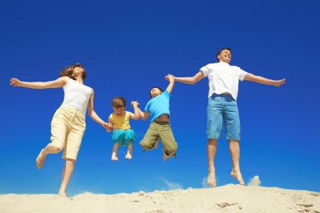 Joyful family jumping together during vacation    Stock Photo