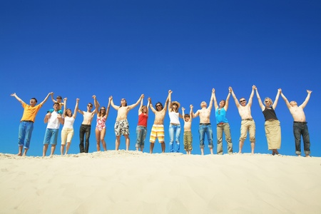 barefoot people: Happy group holding by hands and raising them Stock Photo