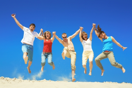 Portrait of five happy people holding by hands and jumping   Stock Photo