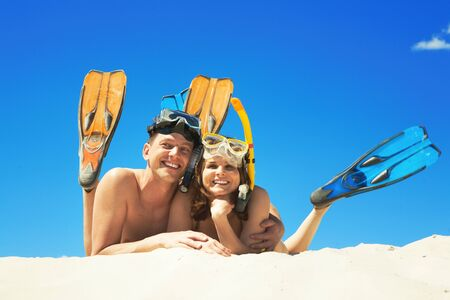 scuba goggles: Happy family with flippers lying on sand and looking at camera