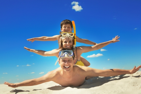 Happy family with flippers lying on sand and looking at camera  photo