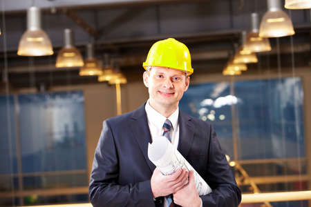 Portrait of confident foreman in helmet holding blueprints photo