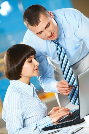 Successful businessman explaining and pointing to laptop with colleague near by photo