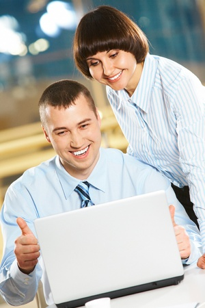 Successful businessman showing sign of ok while looking at the laptop together with woman photo