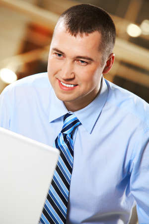 Image of young successful employer looking at laptop monitor on workplace photo