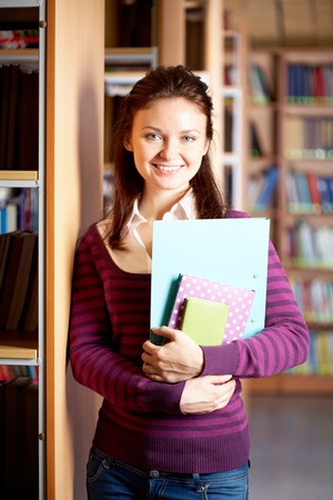 Portrait of clever student with books in college library photo