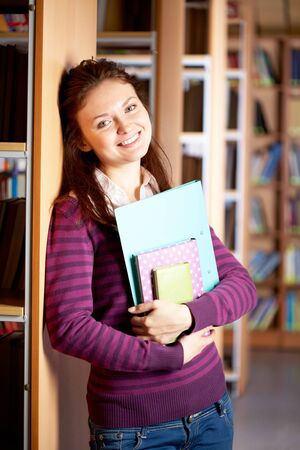 Portrait of clever student with books in college library Stock Photo - 9163909