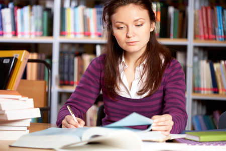 Portrait of clever student searching information for report in college library photo