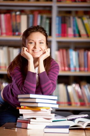 Portrait of clever student looking at camera and smiling in college library photo