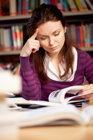 Portrait of serious student searching information for seminar in college library Stock Photo - 9163872