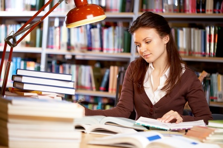 reading lamps: Portrait of clever student searching information for your report in college library Stock Photo