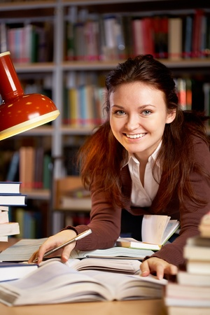 Portrait of young smiling teacher looking at camera in college library photo