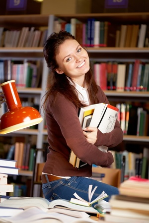 Portrait of clever student or young teacher with books looking at camera and smiling in college library photo