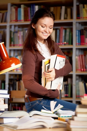 Portrait of clever student or young teacher with books smiling in college library photo