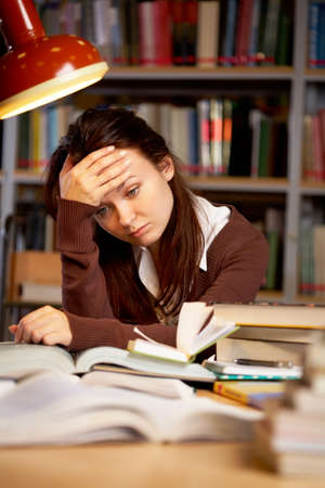 Portrait of troubled girl touching forehead while preparing for seminar in college library photo