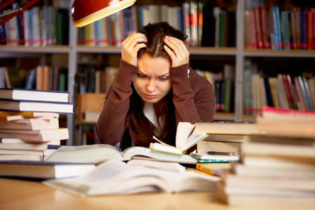 sad teen: Portrait of troubled girl touching head while preparing for seminar in college library Stock Photo