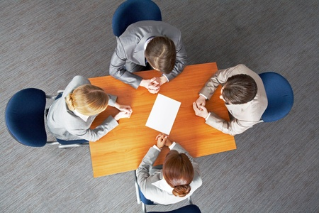 Above view of business people around table with blank paper in center photo