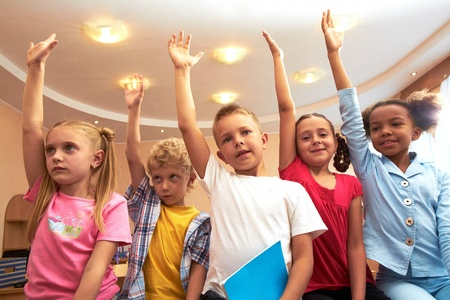 Portrait of several kids raising arms during lesson in classroom photo