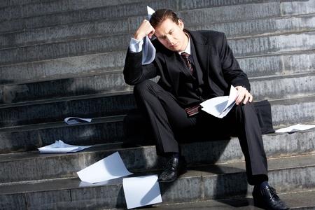 Foto van triest zakenman zittend op de trappen van gebouw Stockfoto