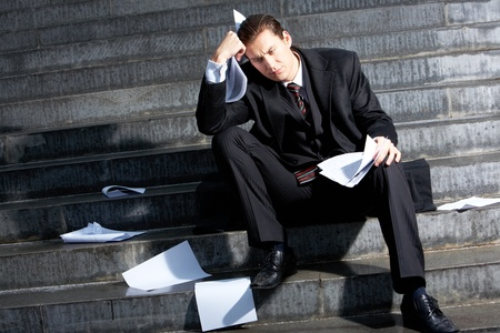 Photo of sad businessman sitting on the stairs of building photo