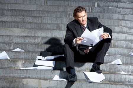 Businessman sitting on the stairs of building and looking at document photo