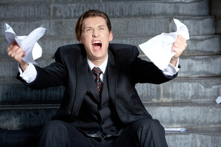 wanhopig: Image of angry businessman with papers in hands raising its  Stockfoto