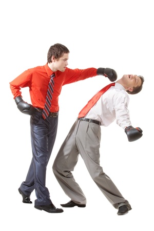 Portrait of aggressive businessman in boxing gloves kicking his rival photo