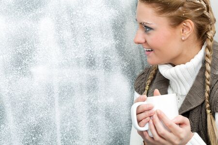 Amazed female with cup in hands looking through frosty window photo