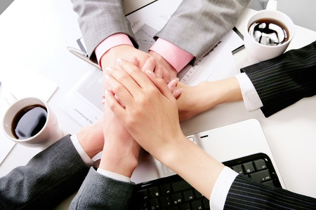 companions: Hands of companions making pile at workplace Stock Photo