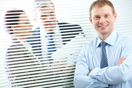 Confident businessman looking at camera in working environment photo