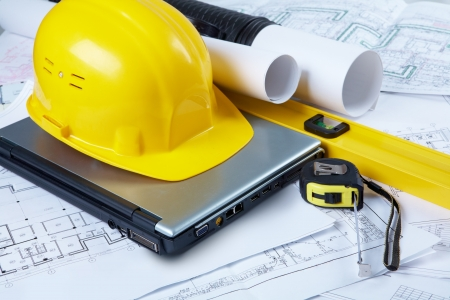 Image of yellow helmet over laptop with ruler placed on blueprint of house  photo