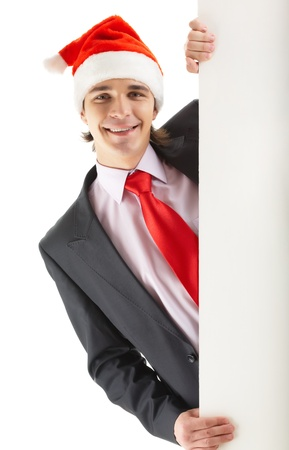 Man with santa hat peeking out of blank poster photo