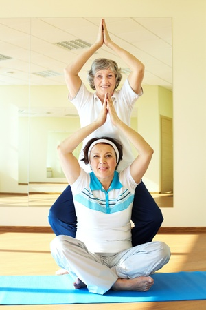 altogether: Portrait of two aged females doing yoga exercise in sport gym