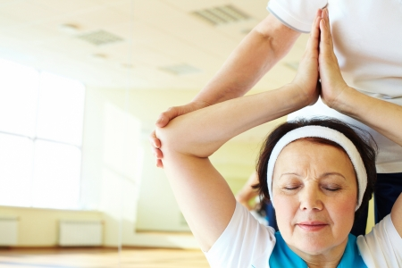 Portrait of aged female doing yoga exercise in sport gym  photo