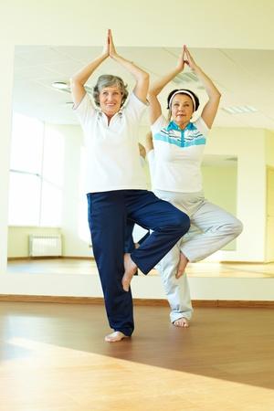 actividad fisica: Retrato de dos mujeres de edad haciendo ejercicios de yoga en el gimnasio de deporte