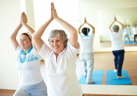 active senior: Portrait of two aged females doing yoga exercise in sport gym