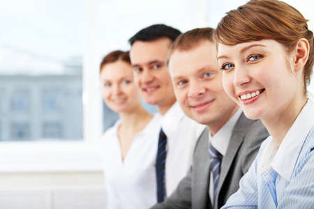 Portrait of friendly leader looking at camera with three employees behind photo