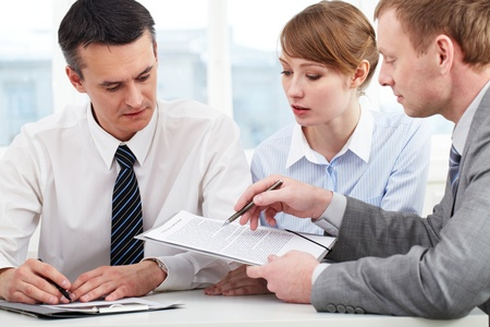 serious meeting: Photo of confident employees discussing papers at meeting  Stock Photo