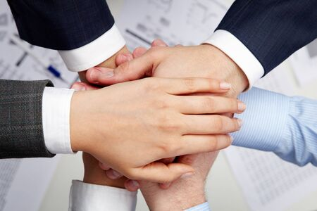 fingers on top: Image of business partners hands on top of each other symbolizing companionship and unity