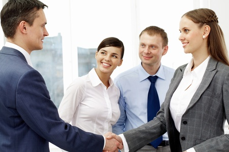 Photo of successful associates handshaking after striking deal with partners near by Stock Photo - 9263001