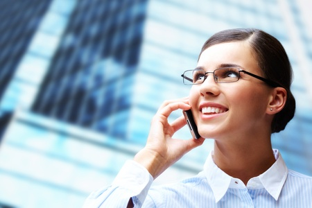 Photo of smart businesswoman calling somebody by mobile telephone photo