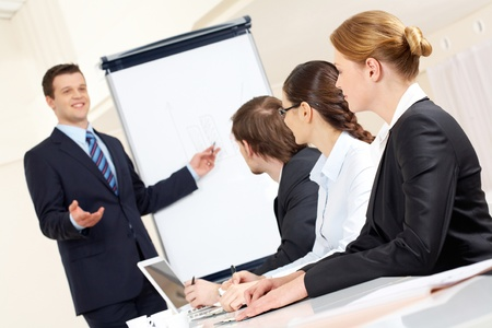 Photo of successful businessman sharing ideas by whiteboard with partners at presentation Stock Photo - 9262250