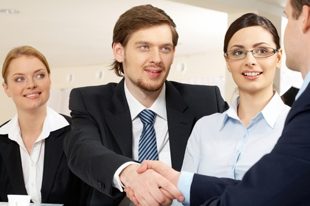Photo of successful business partners handshaking after striking deal with pretty employees near by photo
