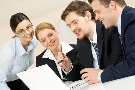 Portrait of friendly workteam looking at monitor of laptop while confident businessman pointing at screen Stock Photo - 9262263