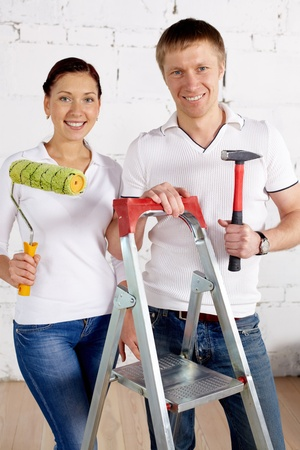 industrious: Industrious couple with paint roll and hammer looking at camera in new house Stock Photo
