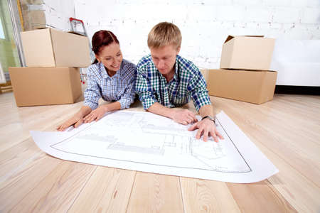 Young couple lying on the floor and looking at blueprint of new house photo