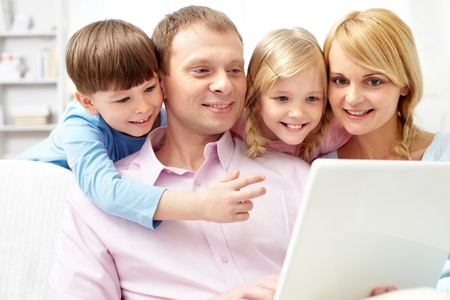 A young family of four using laptop at home photo