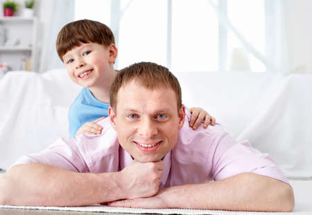 A father and his cute son lying on the floor and looking at camera Stock Photo - 9262151