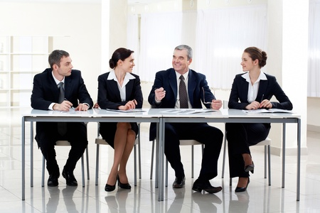 Portrait of smart business people sitting at table and interacting photo