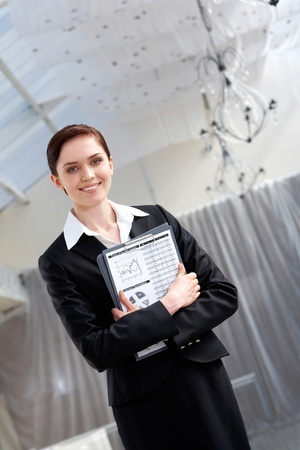 Portrait of pretty female with clipboard in hands looking at camera with smile photo